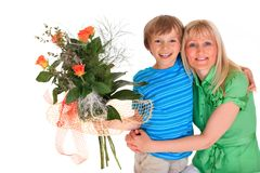 Boy giving mother flowers. Close up of smiling young boy giving mother bouquet of flowers, isolated on white background Royalty Free Stock Photo