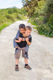 Boy piggyback friend. Young boy piggyback his friend playing outdoors Royalty Free Stock Images