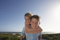 Boy Giving Sister Piggyback Ride Outdoors Royalty Free Stock Photos