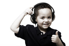 Boy giving thumbs up. Young boy removing headphones giving thumbs up sign Royalty Free Stock Images