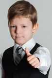 Boy giving thumbs up sign. Portrait of schoolboy showing thumbs up gesture,  selective focus Stock Photos