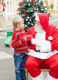 Boy Giving Wish List To Santa Claus Stock Image