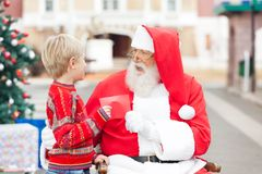 Boy Giving Wish List To Santa Claus Royalty Free Stock Photography