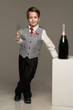 Boy with glass and champagne. Little boy with glass and champagne Royalty Free Stock Images