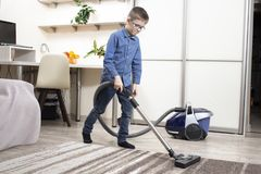 The boy in glasses and a blue shirt is cleaning the flat. Vacuuming the apartment with a vacuum cleaner by a school-age boy.
