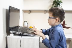 Boy in glasses and a blue shirt is sitting at a desk in front of a laptop and playing a computer game. stock image