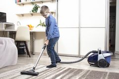 The boy in the glasses cleans the room. Vacuuming the carpet with a vacuum cleaner.