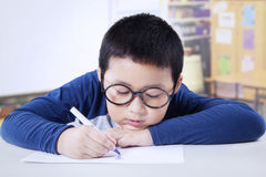 Boy with glasses drawing in class Stock Photo