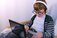 Boy in glasses and earphones is writing on laptop. Online study and learning. royalty free stock photos