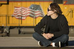 Boy with glasses in front of boxcar Royalty Free Stock Photography