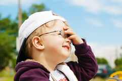 Boy in glasses hand covers the eyes from bright sun Stock Images