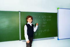 Boy with glasses holds chalk near blackboard Stock Images