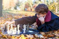 Boy in glasses lies in autumn park with gold leaves, plays chess, makes move, wears in black suit royalty free stock image