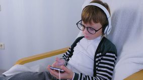Boy in glasses is listening music in headphones in smartphone sitting in armchair at home. Boy in glasses is listening music in headphones in smartphone sitting stock video