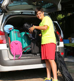 Boy with glasses loads the luggage in the trunk of the car. Young boy with glasses loads the luggage in the trunk of the car during the travel of the holidays Royalty Free Stock Image