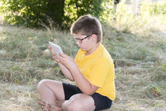 The boy in glasses looks tablet computer at nature Royalty Free Stock Photography