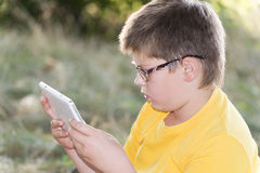 The boy in glasses looks tablet computer at nature Stock Photography