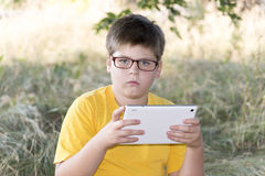 The boy in glasses looks tablet computer at nature Stock Images