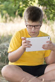 The boy in glasses looks tablet computer at nature Royalty Free Stock Photo