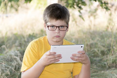 The boy in glasses looks tablet computer at nature Stock Image