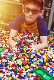 Boy in glasses play with many toys. royalty free stock photos