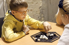 Boy in glasses playing Abalone strategy board game Royalty Free Stock Photos
