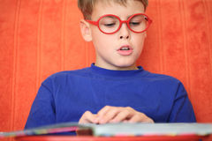 Boy reading a book intently. Boy with glasses reading a book intently Royalty Free Stock Photos