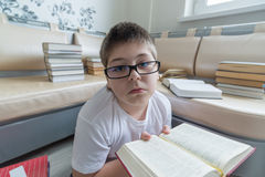 Boy with glasses reading a book in  room Stock Photography
