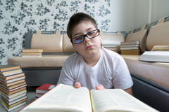 Boy with glasses reading a book in  room Royalty Free Stock Photo