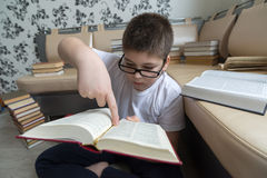Boy with glasses reading a book in  room Royalty Free Stock Photography