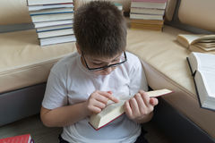 Boy with glasses reading a book in  room Stock Photos