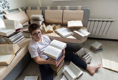 Boy with glasses reading a book in  room Stock Image