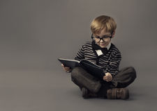 Boy in glasses reading book, smart little child st Royalty Free Stock Image
