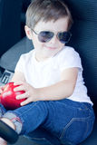 Boy with glasses and  red apple sitting in car Royalty Free Stock Images