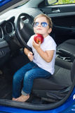 Boy with glasses and  red apple sitting in car Royalty Free Stock Photo