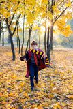 boy in glasses runs in autumn park with gold leaves, holds book in his hands royalty free stock photography