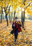 Boy in glasses runs in autumn park with gold leaves, holds book in his hands, wears in black robe stock images
