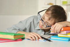Boy in glasses sleeps on books. Portrait of a boy in glasses sleeps on books Stock Photo
