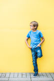 Boy with glasses standing near yellow wall oudoors Stock Photography