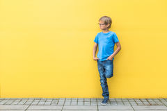 Boy with glasses standing near yellow wall oudoors Royalty Free Stock Photography