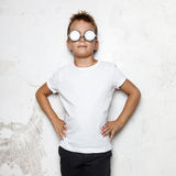 Boy with glasses stands on a wall background and stock photos