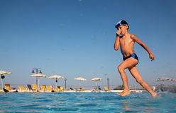 Boy with glasses for swimming dives into water. Little boy with glasses for swimming dives into blue, clear water of pool. in background beach umbrellas. from Stock Images