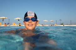 Boy with glasses for swimming swim in pool. Little boy with glasses for swimming and bathing cap, swim in pool. in background beach umbrellas. from the Stock Photos
