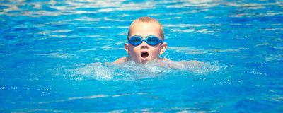 The boy in glasses for swimming swims in the pool. The boy in glasses stock images