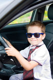 Boy with glasses and tie in car Royalty Free Stock Image