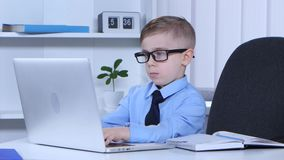 Boy in glasses is typing on a laptop and the data recorded in notes. Little boy office worker with glasses and shirt prints in the laptop and the data recorded stock footage