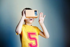 Boy with glasses of virtual reality. Future technology concept. Modern imaging technology. Little child uses virtual reality VR cardboard on blue background Stock Photo