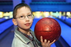Boy in glasses, which hold ball for bowling Royalty Free Stock Photos