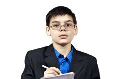 A boy with glasses writes Royalty Free Stock Photos