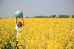 Boy with globe. Young boy holding up a globe standing in colza field stock photo